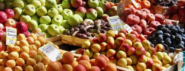 aprictos nectarines plums apples and other fruit at a market stall