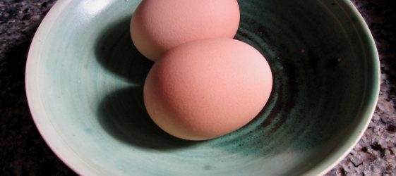 two eggs in shell in small green bowl