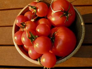 bowl of small and medium sized tomatoes in the sun in a brown pottery bowl recipe braised tomatoes