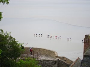 aerial view of grey beach with a line of children in multicoloured coats France
