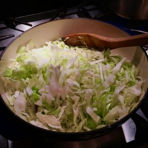 white and green sliced cabbage in a white enamel pot on stove with wooden spoon ©gillstannard naturopath