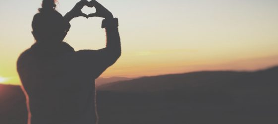 silhouette of woman holding hands in heart shape against a sunset