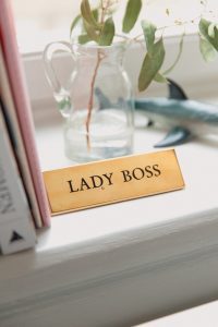 bronze plaque with words lady boss, on a window sill beside a pink book and a glas vase with a green leaf in it