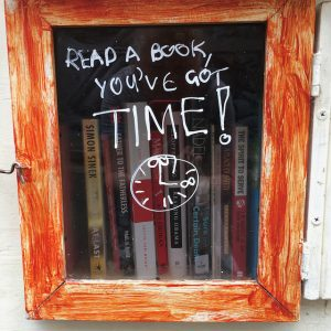 "street library orange painted wood around a glass window with read a book you've got time"" written in white texta"