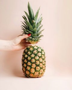 upright pineapple with hand holding the crown