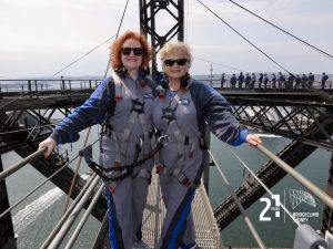 Two women in sunglasses and grey and blue overalls on top of Sydney harbour bride holding wire railing with metal tower and australian flag in background. Green water below.