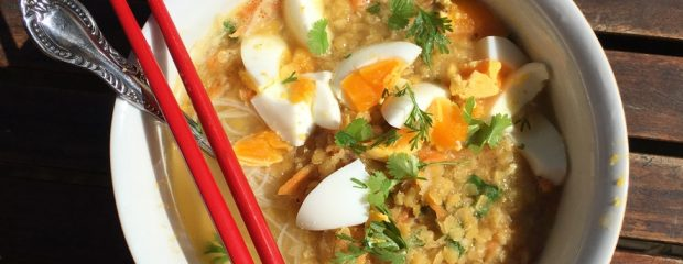 white bowl containing red lentil soup, rice noodles and quartered boiled egg garnished with coriander a spoon sits in the bowl and a pair of red chopsticks across the top