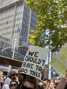 tall buildings in background foreground hands hold a hand written sign saying we shouldn't have to do this