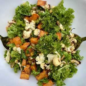 green kale, florets of roasted cauliflower, cubed sweet potato sald on a white plate with silver salad servers