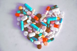 different coloured pills and capsules arranged in a heart shape