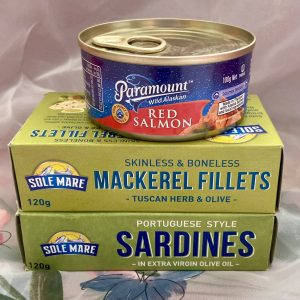 stack of tinned seafood on white background mackeral fillets, sardines, can paramount red salmon