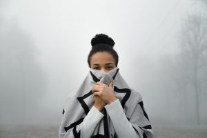 woman of colour with dark hair in a bun at top of head holds gray and black geometric striped scarf of pbdy and lower face background white mist it looks cold